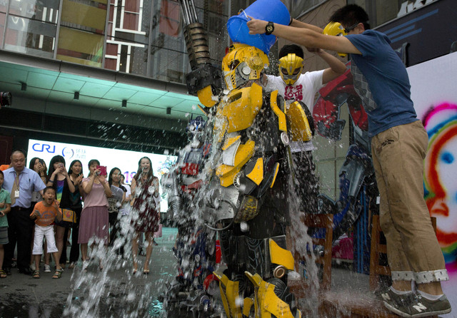 """A man dressed as Bumble Bee, a character from the Transformers movies, takes the """"Ice Bucket Challenge"""" to raise awareness for the disease ALS in Beijing, China,  Aug. 20, 2014. The phenomenal suc ..."""