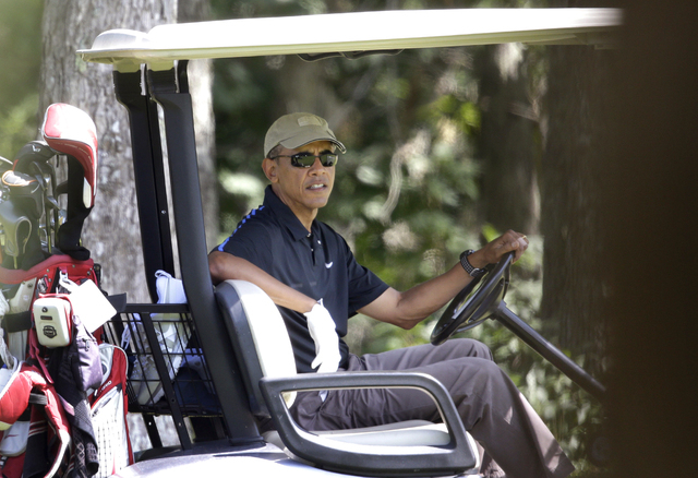 President Barack Obama sits in a golf cart while golfing at Farm Neck Golf Club, in Oak Bluffs, Mass., on the island of Martha's Vineyard, Thursday, Aug. 21, 2014. Obama is vacationing on the isla ...