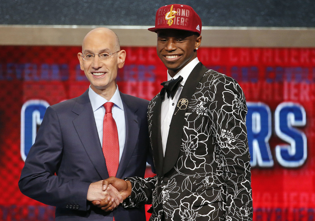 In this June 25, 2014, file photo, NBA Commissioner Adam Silver, left, congratulates Andrew Wiggins of Kansas who was selected by the Cleveland Cavaliers as the No. 1 pick in the 2014 NBA basketba ...