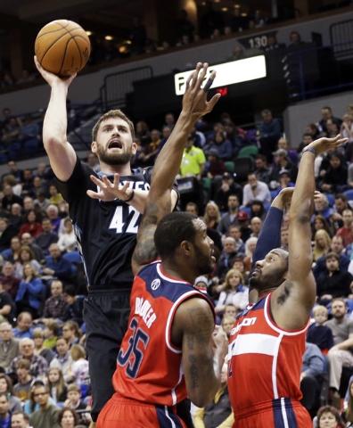 In this Dec. 27, 2013, file photo, Minnesota Timberwolves' Kevin Love (42) shoots over Washington Wizards' Trevor Booker (35) and John Wall during the first quarter of an NBA basketball game in Mi ...