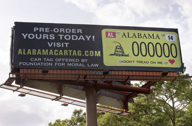 A billboard showing a license plate and slogan stands alongside Interstate 85 on Saturday, Aug. 23, 2014, in Montgomery, Ala. (AP Photo/Brynn Anderson)