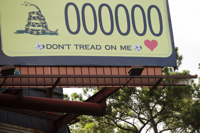 A billboard showing a license plate and slogan stands alongside Interstate 85 on Saturday, Aug. 23, 2014, in Montgomery, Ala. Alabama vehicles could soon be sporting tags featuring the rattlesnake ...