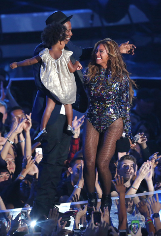 Beyonce accepts the Video Vanguard Award at the MTV Video Music Awards at The Forum on Sunday, Aug. 24, 2014, in Inglewood, Calif. Looking on from left is Blue Ivy and Jay-Z. (Photo by Matt Sayles ...