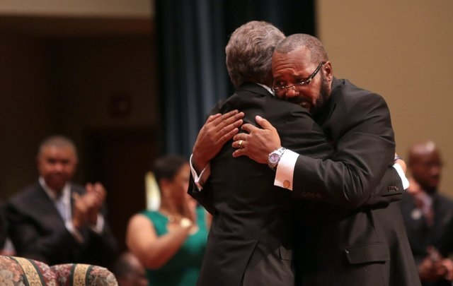 Pastor Charles Ewing, right, uncle of Michael Brown Jr., embraces Rev. Al Sharpton during the funeral services for Brown on Monday, Aug. 25, 2014, at Friendly Temple Missionary Baptist Church in S ...