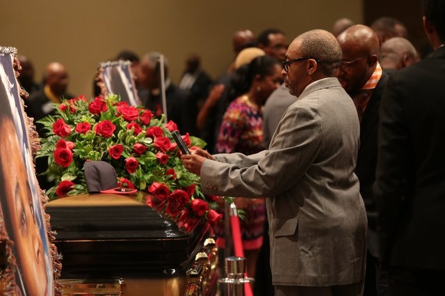Director Spike Lee takes a picture of a black St. Louis Cardinals baseball cap on top of Michael Brown's casket on Monday, Aug. 25, 2014, during the funeral services at Friendly Temple Missionary  ...