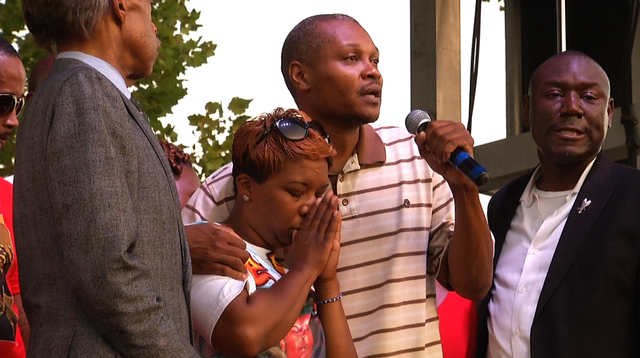 Lesley McSpadden, Michael Brown's mother, second from left, stands next to her cousin, Eric Davis, as he addresses  the crowd at Peace Fest, Sunday, Aug. 24, 2014, in St. Louis. Hundreds of people ...