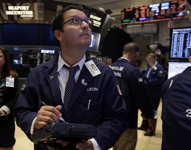 FILE - In this Tuesday, Aug. 19, 2014, file photo, trader Leon Montana works on the floor of the New York Stock Exchange. U.S. stocks opened slightly higher on Tuesday, Aug. 26, 2014, as investors ...