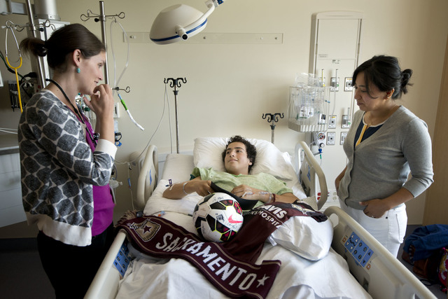 Child care specialist Emily McDaniel, left, checks on Nicholas Dillion, whose aunt, Carmen Rosales stands next to his bed where he rests at UC Davis Medical Center on Tuesday, Aug. 26, 2014, in Sa ...