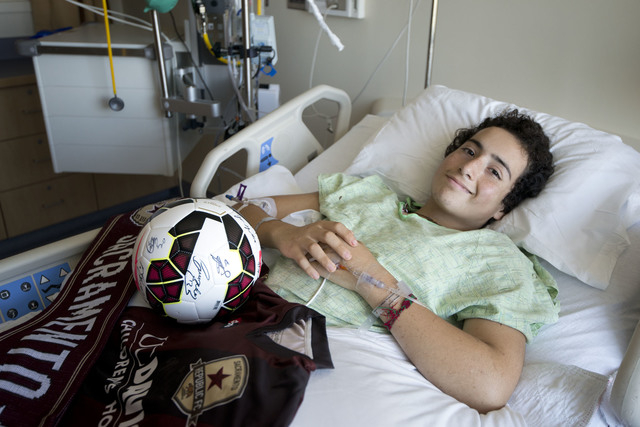 Nicholas Dillion rests in his bed at UC Davis Medical Center with soccer gifts given to him by Republic FC soccer player Max Alvarez on Tuesday, Aug. 26, 2014, in Sacramento, Calif., after being i ...