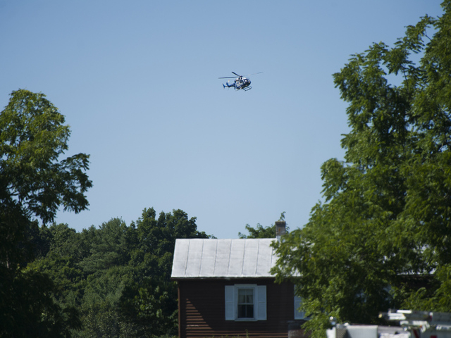 A Virginia State Police search helicopter hovers close to the scene where an Air Force F-15C fighter jet based in Massachusetts crashed near Deerfield, Va., Wednesday, Aug. 27, 2014. The jet was o ...