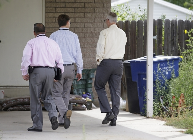 Police walk near garbage cans where a baby was found Tuesday, Aug. 26, 2014, in Kearns, Utah. Police say the newborn, who was left in the trash can near the mother's home, is in extremely critical ...