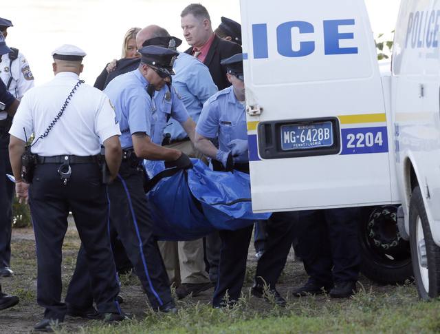 Philadelphia police load a body pulled from the Schuylkill River in Fairmount Park into a vehicle in Philadelphia, Wednesday, Aug. 27, 2014. The bound bodies of two people were found in the river  ...