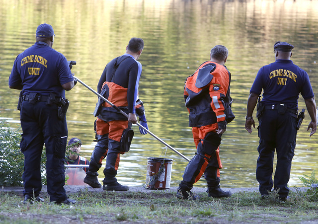 Philadelphia police remove a bucket from the Schuylkill River in Fairmount Park as they investigate, in Philadelphia, Wednesday, Aug. 27, 2014.  The bound bodies of two people were found in the ri ...