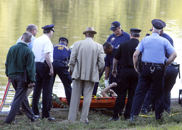 Philadelphia police and other law enforcement officials view a body pulled from the Schuylkill River in Fairmount Park in Philadelphia, Wednesday, Aug. 27, 2014.  The bound bodies of two people we ...