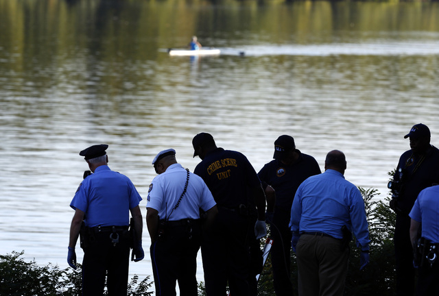 Philadelphia police and other law enforcement officials work along the Schuylkill River in Fairmount Park in Philadelphia, Wednesday, Aug. 27, 2014. The bound bodies of two people were found in th ...
