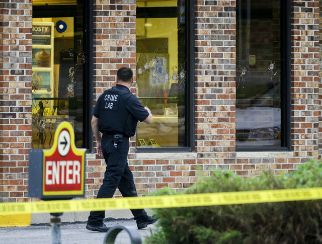 "A crime lab technician walks past bullet riddled windows at a Wendy's in Omaha, Neb., Wednesday, Aug. 27, 2014. Police say a suspect has been killed and a crew member with the ""Cops"" tel ..."