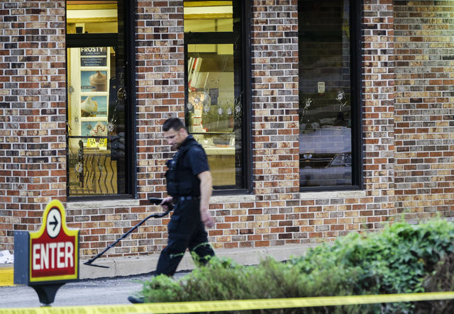 A clime lab technician carries a metal detector past bullet holes in the windows of a Wendy's in Omaha, Neb., Wednesday, Aug. 27, 2014. Police say a suspect has been killed and a crew member with  ...
