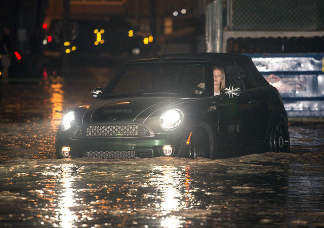 A woman drives through a flooded street after high tide and large waves caused heavy flooding in Seal Beach, California, Tuesday, Aug. 26, 2014. A low-lying street in the Southern California coast ...