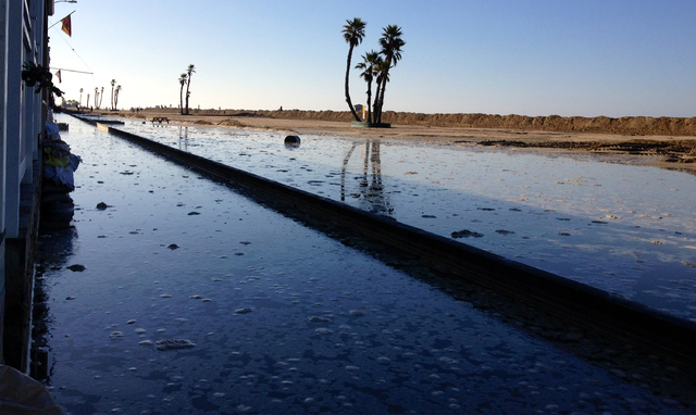 Beach front property is flooded after high tide and large waves caused heavy flooding in Seal Beach, California, on Wednesday, Aug. 27, 2014. A low-lying street in the Southern California coastal  ...