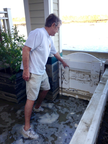 Resident Jerry Rootlieb points to the high water line on his gate, Wednesday, Aug. 27, 2014, after heavy flooding in Seal Beach, California.  A low-lying street in the Southern California coastal  ...