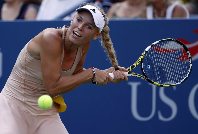 Caroline Wozniacki, of Denmark, gets her hair caught in her racket as she tries to return a shot to Aliaksandra Sasnovich, of Belarus, during the second round of the 2014 U.S. Open tennis tourname ...