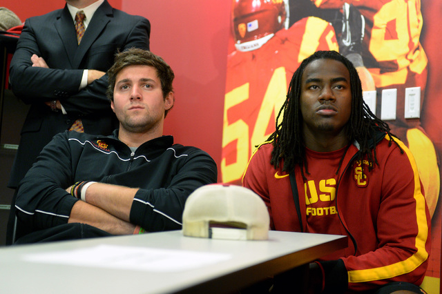 In this Dec. 3, 2013, file photo, Southern California quarterback Cody Kessler, left, and Josh Shaw watch a news conference for USC's new football coach Steve Sarkisian in Los Angeles. Shaw has ad ...
