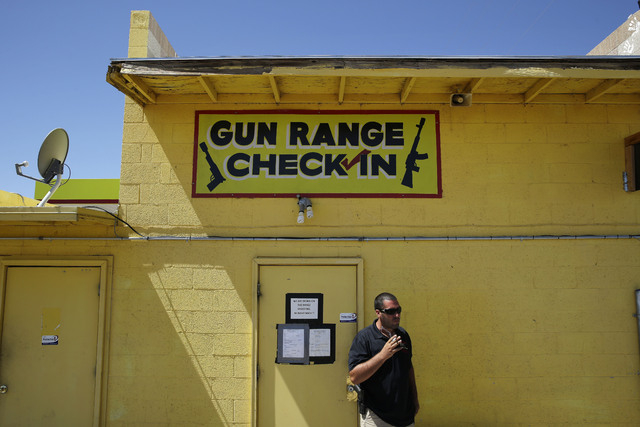 An employee smokes outside of an office for the Last Stop outdoor shooting range Wednesday, Aug. 27, 2014, in White Hills, Ariz. Instructor Charles Vacca was accidentally killed at the range by a  ...