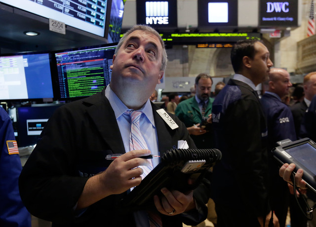 FILE - In this Thursday, Aug. 21, 2014, file photo, trader Edward McCarthy, left, works on the floor of the New York Stock Exchange. As stocks continue to rise, investors are wondering if its time ...