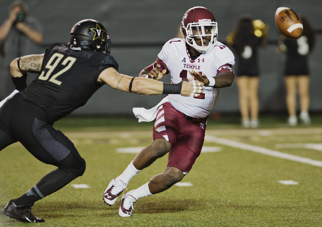 Temple quarterback P.J. Walker (11) tosses the ball before getting hit by Vanderbilt's Kyle Woestmann (92) in the first quarter of an NCAA college football game Thursday, Aug. 28, 2014, in Nashvil ...