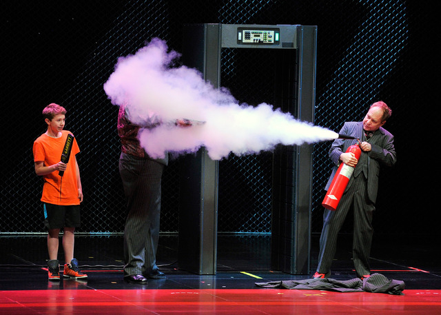 Penn Jillette, hidden behind the smoke, and Teller, right, of Penn & Teller, perform with a member of the audience during their show at the Rio on Monday, Aug. 18, 2014. (David Becker/Las Vegas Re ...