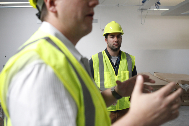 Micah Lillard, center, public relations specialist, listens to Keith Hansen, director of facilities, during a tour of the new corporate headquarters of Allegiant Air, 1201 N. Town Center Dr. in La ...