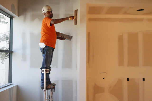 Construction taper Adrian Flores prepares a wall for painting at the future corporate headquarters of Allegiant Air, 1201 N. Town Center Dr. in Las Vegas during a tour Wednesday, Aug. 27, 2014. Th ...