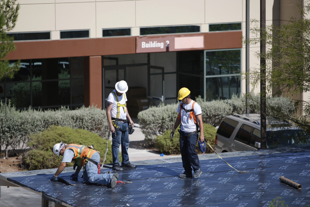 Construction workers work on the roof of a building at the future corporate headquarters site for Allegiant Air, 1201 N. Town Center Dr. in Las Vegas Wednesday, Aug. 27, 2014. The project is sched ...