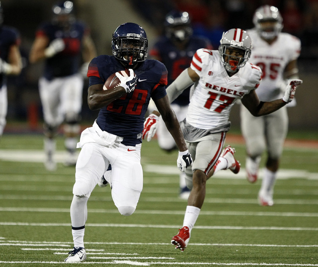 Arizona running back Nick Wilson (28) scores a touchdown against UNLV during the second half of an NCAA college football game, Friday, Aug. 29, 2014, in Tucson, Ariz. (AP Photo/Rick Scuteri)