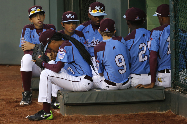 Philadelphia pitcher Mo'ne Davis, center from left, waits to take the field with her teammates for a United States semi-final baseball game against Las Vegas at the Little League World Series tour ...