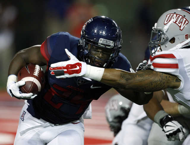 Arizona running back Terris Jones-Grigsby (24) runs for 45 yards against /uu/ during the first half of an NCAA college football game, Friday, Aug. 29, 2014, in Tucson, Ariz. (AP Photo/Rick Scuteri)