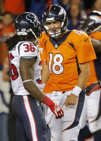 Denver Broncos quarterback Peyton Manning (18) talks to Houston Texans strong safety D.J. Swearinger (36) after a Broncos touchdown during the first half of an NFL preseason football game, Saturda ...