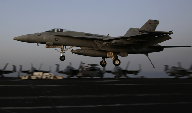An F/A-18C Hornet coming from Iraq lands on the flight deck of the U.S. Navy aircraft carrier USS George H.W. Bush, Sunday, Aug. 10, 2014, in the Persian Gulf. Aircraft aboard the George H.W. Bush ...