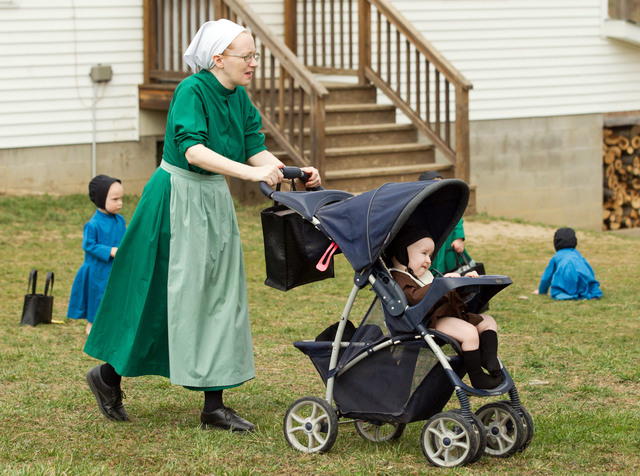 Emma Miller pushes her son in a stroller outside the schoolhouse in Bergholz, Ohio, April 9, 2013. Miller, along with three other women and a man from this tight-knit community in rural eastern Oh ...