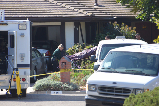 Investigators remove a body from a home in Goleta, Calif., Tuesday, Aug. 12, 2014, where four people and a dog were found stabbed to death the night before. Authorities said the sole suspect, a 46 ...