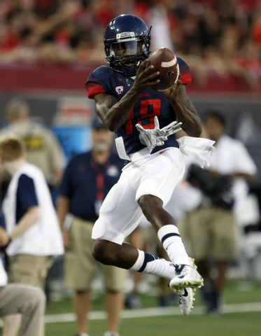 Arizona running back Davonte' Neal (19) warms up before an NCAA college football game against UNLV, Saturday, Aug. 29, 2014, in Tucson, Ariz. (AP Photo/Rick Scuteri)
