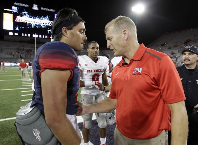 Arizona quarterback Anu Solomon (12) and UNLV head coach Bobby Hauck talk after an NCAA college football game, Friday, Aug. 29, 2014, in Tucson, Ariz. (AP Photo/Rick Scuteri)