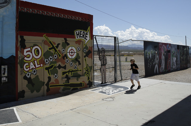A young person runs by the Last Stop outdoor shooting range Wednesday, Aug. 27, 2014, in White Hills, Ariz. Gun range instructor Charles Vacca was accidentally killed Monday, Aug. 25, 2014, at the ...
