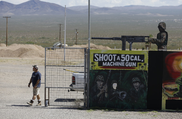 A man closes off an entrance to the Last Stop outdoor shooting range Wednesday, Aug. 27, 2014, in White Hills, Ariz. Gun range instructor Charles Vacca was accidentally killed Monday, Aug. 25, 201 ...