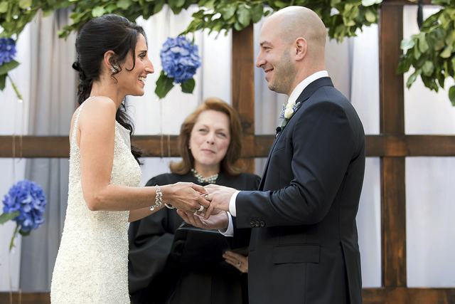 In this photo taken on Saturday, Aug. 23, 2014, and released by Hyatt Regency Boston, Boston Marathon bombing survivor, James Costello, right, marries Krista D'Agostino  at the hotel in Bos ...