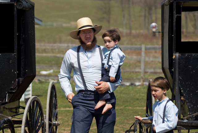 Freeman Burkholder carries his son to the school house for a ceremony to mark the end of the school year April 9, 2013, in Bergholz, Ohio. Burkholder was convicted with 15 other men and women in h ...