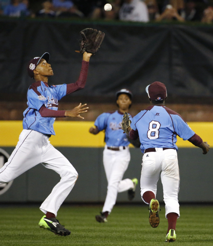 Philadelphia center fielder Kai Cummings, left, runs under a fly ball, that second baseman Jahli Hendricks (8) can't get to,  hit by Las Vegas'  Andrew Matulich in the sixth inning of a United Sta ...