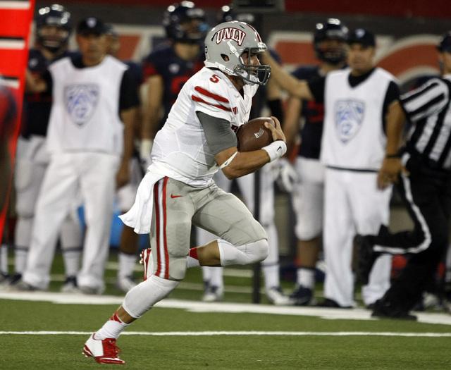 UNLV quarterback Blake Decker carries against Arizona during the first half of an NCAA college football game, Friday, Aug. 29, 2014, in Tucson, Ariz. (AP Photo/Rick Scuteri)