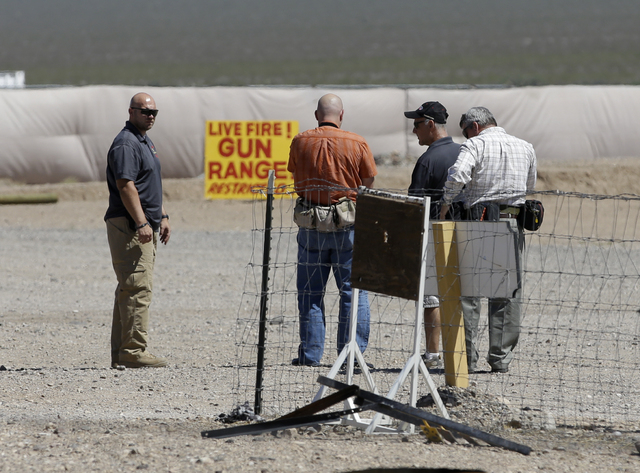 People are seen at the Last Stop outdoor shooting range Wednesday, Aug. 27, 2014, in White Hills, Ariz. Gun range instructor Charles Vacca was accidentally killed Monday, Aug. 25, 2014, at the ran ...
