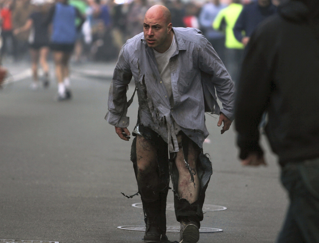 In this photo provided by The Daily Free Press and photographer Kenshin Okubo, Boston Marathon bombing victim James Costello staggers away in his torn clothing from the finish area in Boston, Mond ...